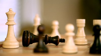 stock-footage-white-chess-player-knocks-down-the-black-king-with-his-piece